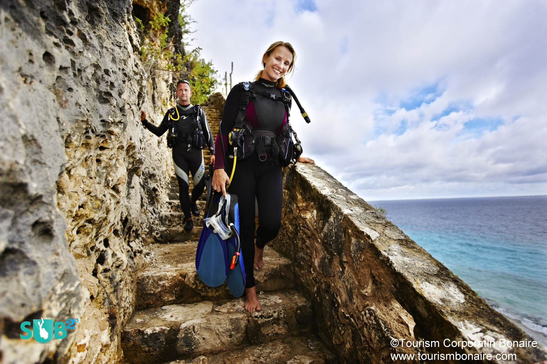 Divers carefully carry their equipment down the 72 steps to begin their dive. Shore entries and exits are clearly indicated, with bright yellow rocks used as markers.