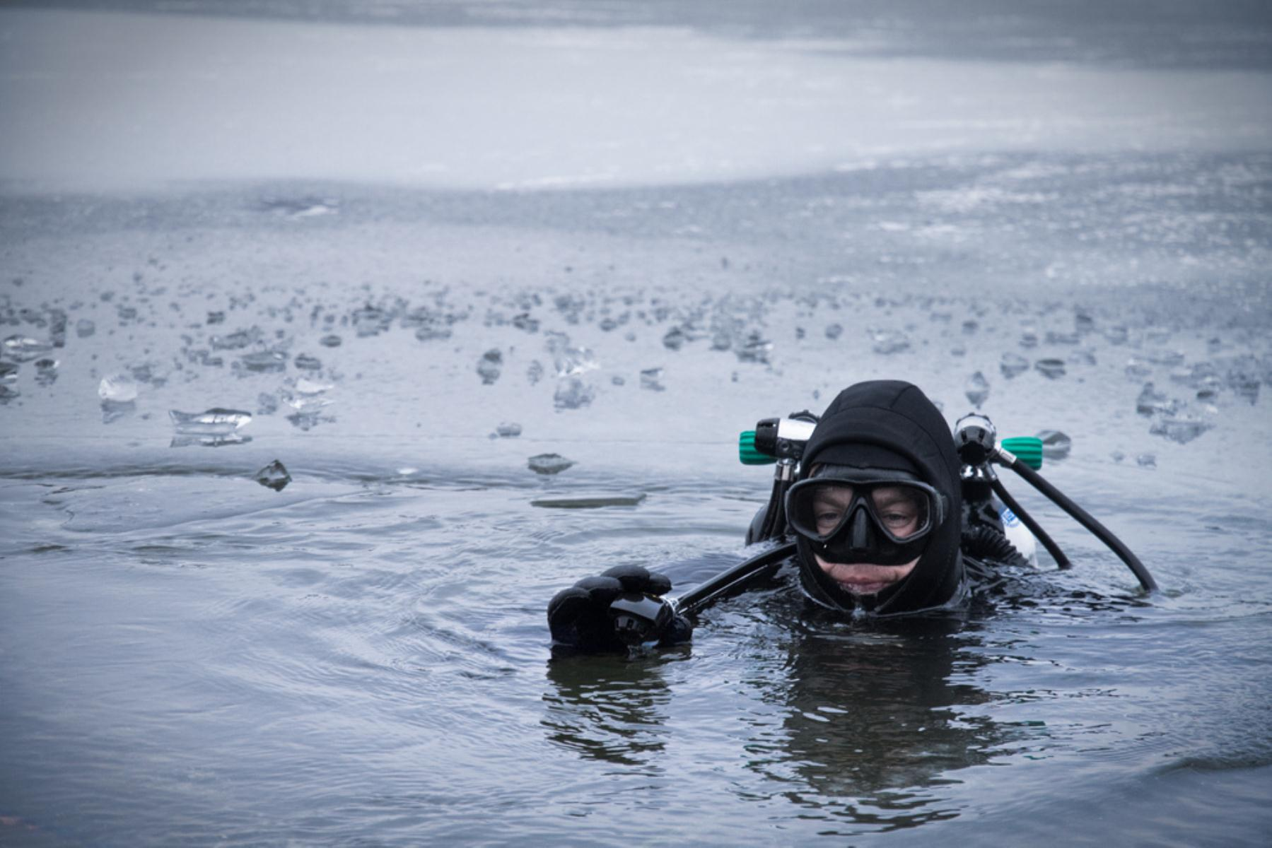 Diver preparing to drop beneath the surface in an icy lake