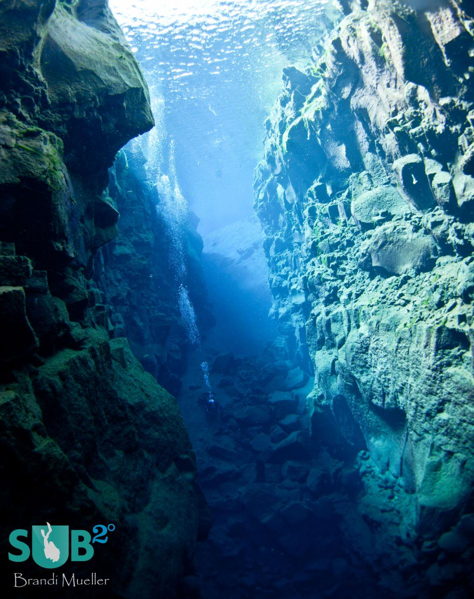 A diver diving in-between the North American and European continental plates at Silfra Crack, Iceland.