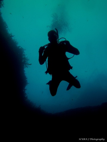 A scuba diver descends to a depth of 45 feet while hovering outside the cavern entrance at Vortex Spring.