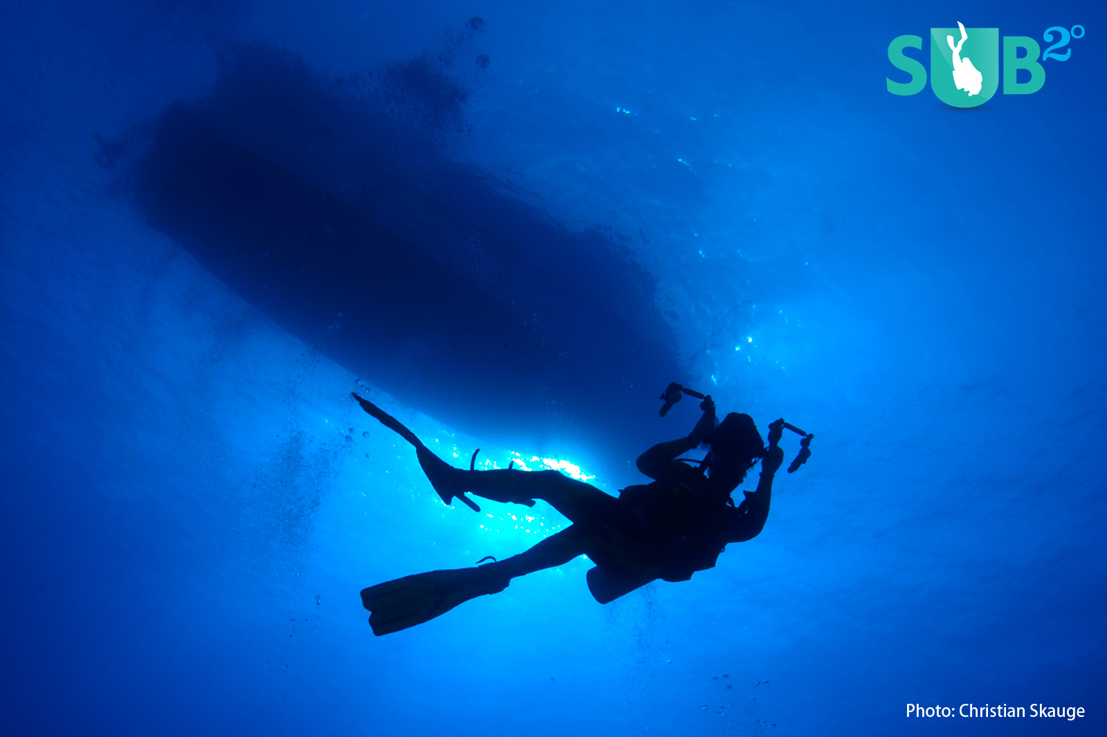 A diver in perfect silhouette against the blue water, with the dive boat at the surface.